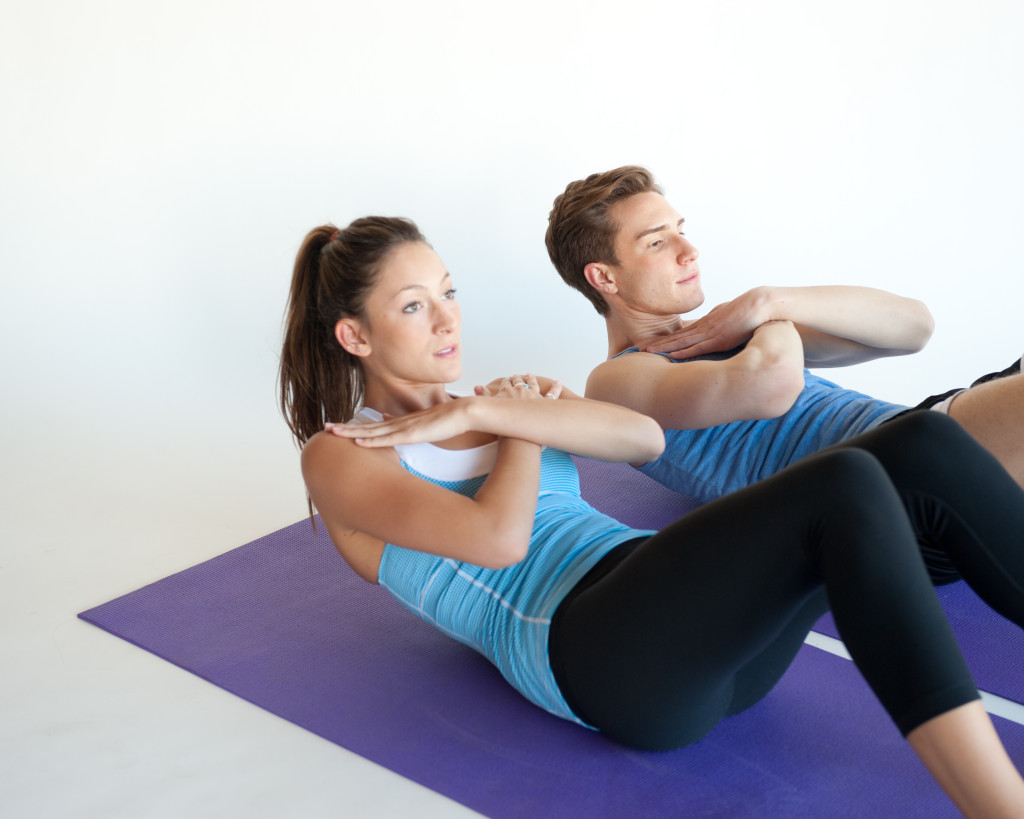 Hombre y mujer haciendo abdominales corrientes con las manos en cruz y al pecho