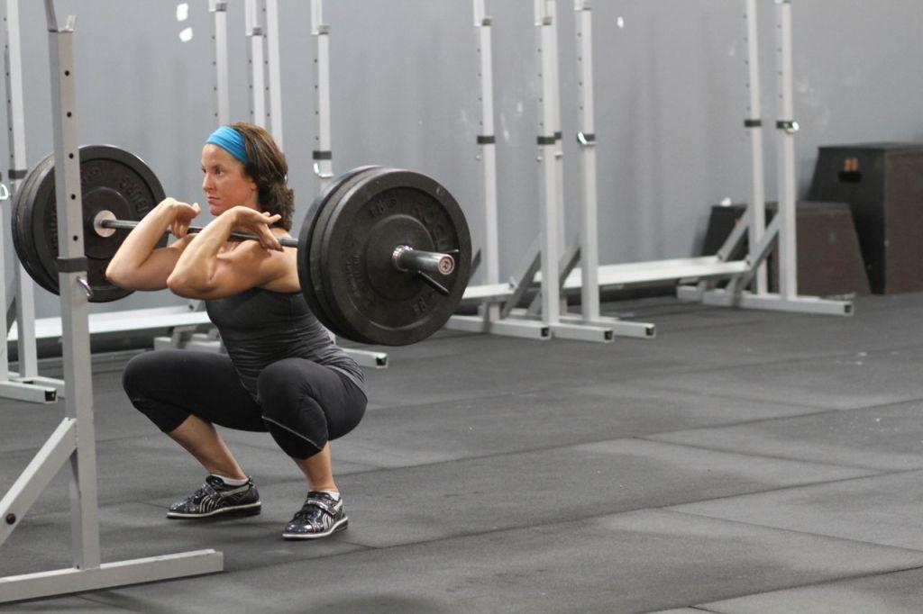 Mujer haciendo sentadillas frontales apunto de realizar movimiento ascendente