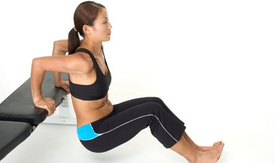 Mujer haciendo fondo de triceps con un banco