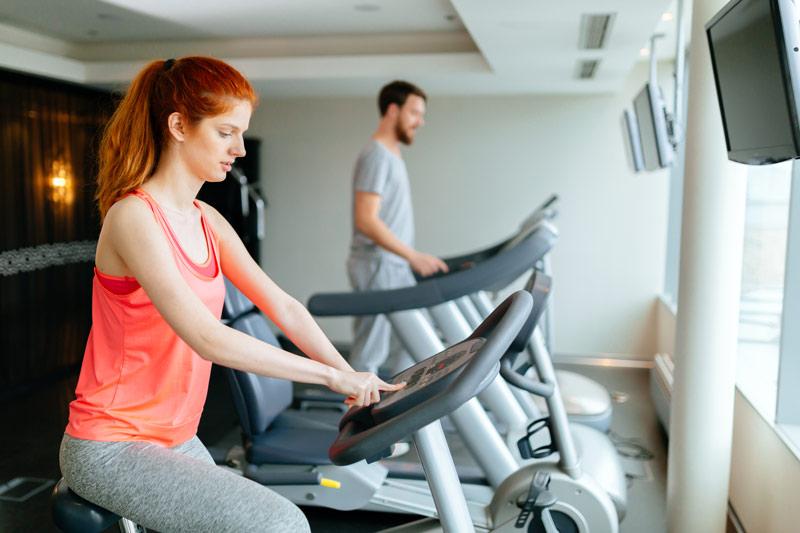 Beneficios de la bicicleta estática mujer entrenando