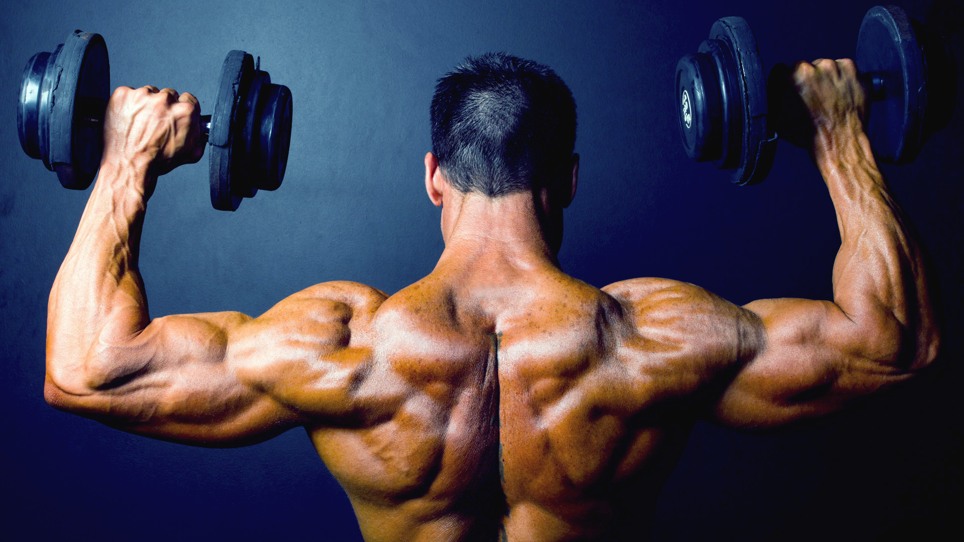 Hombre de espaldas con dos mancuernas press de hombro
