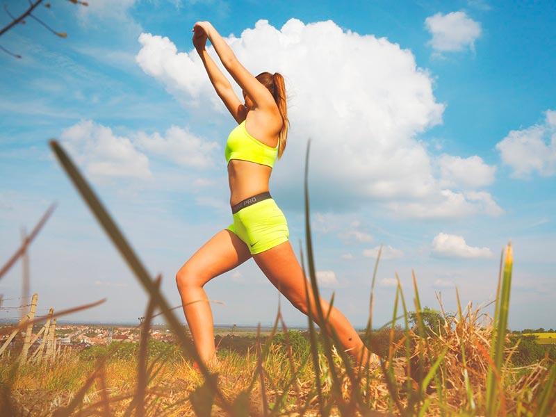 ejercicios-al-aire-libre-mujer-estiramiento-campo