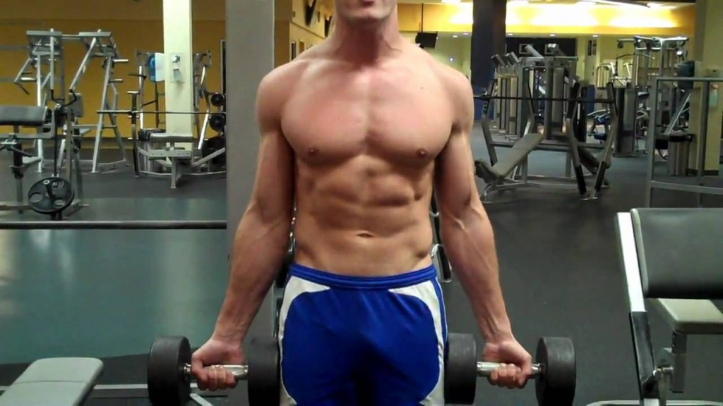 Hombre realizando Curl Zottman en un gimnasio con dos mancuernas
