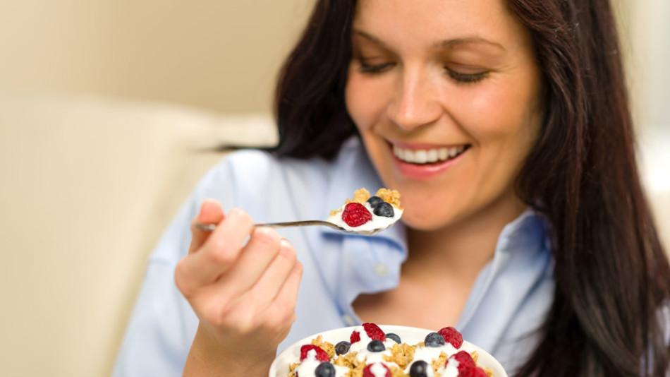 Mujer desayunando cereales con fruta