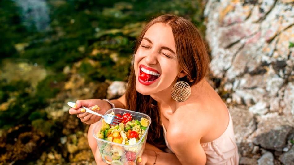 Mujer comiendo ensalada de vacaciones