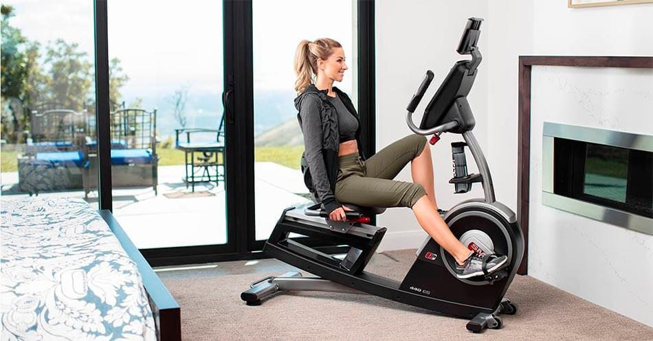 bicicleta-estatica-musculos-que-trabaja-mujer-entrenando-en-casa