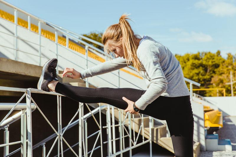 sports woman stretching legs P8WQBLN