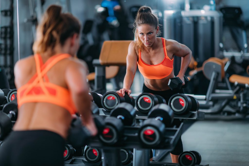 woman exercising with weights in the gym HJKMPJL min