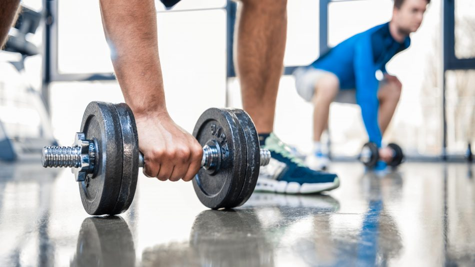 young men workout with dumbbells at gym focus on m QUKCVUE min